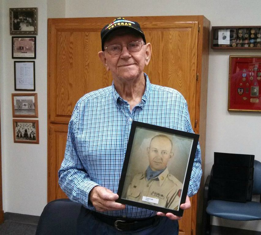 Man in blue plaid shirt and Korea Veteran hat holds up framed picture, and smiles into camera